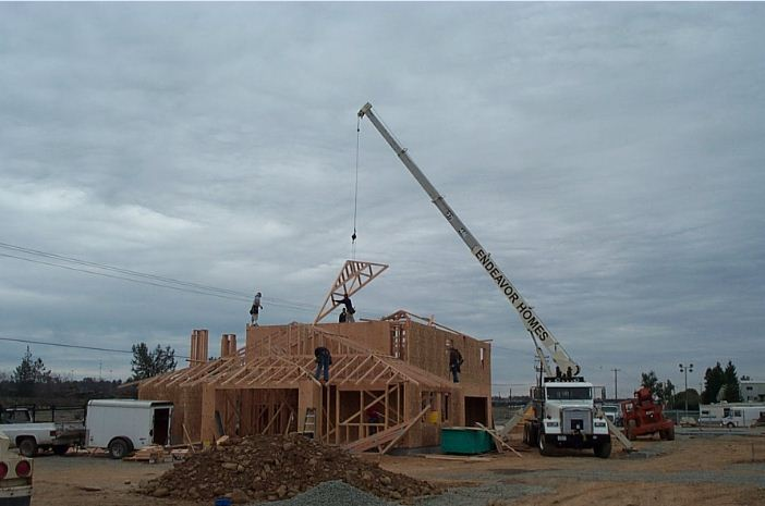 The Endeavor Homes boom truck setting roof trusse on the top plate of a commercial building